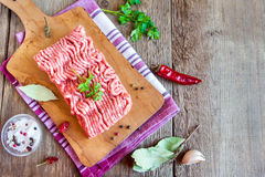 Raw minced meat. Raw homemade minced meat over wooden cutting board with assorted spices, copy space Royalty Free Stock Image