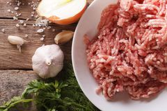 Raw minced meat and ingredients on the table. horizontal top vie. Raw minced meat and ingredients on the table. horizontal view from above, rustic style Royalty Free Stock Images