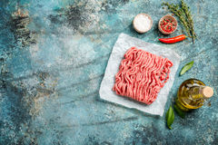 Raw minced meat. With olive oil and seasoning on paper over blue stone background. top view with copy space Royalty Free Stock Image