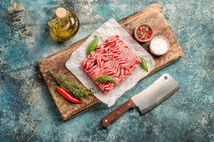 Raw minced meat. With olive oil and seasoning on paper over blue stone background. top view with copy space Stock Photography