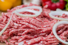 Raw minced meat and onion rings close-up with fresh vegetables on the background Stock Photo