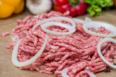 Raw minced meat and onion rings close-up with fresh vegetables on the background. Raw minced meat with onion over fresh vegetables Stock Photo