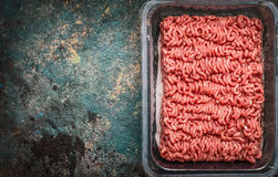 Raw minced meat in plastic box on rustic background, top view Stock Image