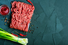 Raw minced meat. On plate and on a table Royalty Free Stock Image