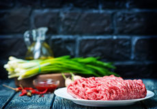 Raw minced meat. On plate and on a table Stock Image