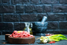 Raw minced meat. On plate and on a table Stock Images