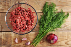 Raw minced meat in a plate on wooden background. Top view Stock Photos