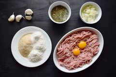 Raw minced meat with seasonings on dark background. minced meat and ingredients on the table. horizontal view from above. Raw minced meat with seasonings on dark Stock Images