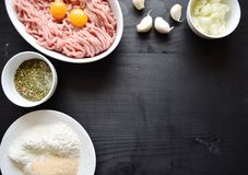 Raw minced meat with seasonings on dark background. minced meat and ingredients on the table. horizontal view from above. Raw minced meat with seasonings on dark Royalty Free Stock Photo