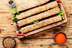 Raw minced meat skewers kebabs. Caucasian popular dish, kebab from young lamb meat and spices.Caucasian kitchen Stock Photos