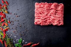 Raw minced meat on slate plate, ingredients for meat with tomato, chili pepper and herbson black background macro top. View Stock Photos