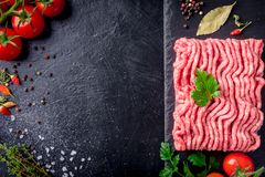 Raw minced meat on slate plate, ingredients for meat with tomato, chili pepper and herbson black background macro top view.  Stock Photos