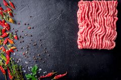Raw minced meat on slate plate, ingredients for meat with tomato, chili pepper and herbson black background macro top view.  Stock Photography