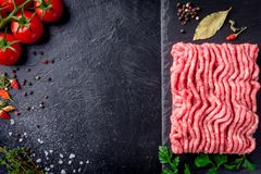 Raw minced meat on slate plate, ingredients for meat with tomato, chili pepper and herbson black background macro top view.  Royalty Free Stock Photos