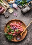 Raw minced meat stuffing in wooden bowl and spoon on gray stone background with meat grinder, and ingredients , top view, place fo. R text. Cooking,recipes and Royalty Free Stock Photography