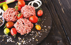 Raw minced meat, vegetables with salt and spices, selective focus. Raw minced meat, vegetables with salt and spices, on a black background, selective focus Royalty Free Stock Photo