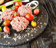 Raw minced meat, vegetables with salt and spices, selective focus. Raw minced meat, vegetables with salt and spices, on a black background, selective focus Stock Images