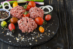 Raw minced meat, vegetables with salt and spices, selective focus. Raw minced meat, vegetables with salt and spices, on a black background, selective focus Stock Photos