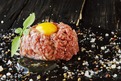 Raw minced meat, vegetables with salt and spices, selective focus. Raw minced meat, vegetables with salt and spices, on a black background, selective focus Royalty Free Stock Photography