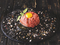 Raw minced meat, vegetables with salt and spices, selective focus. Raw minced meat, vegetables with salt and spices, on a black background, selective focus Stock Image
