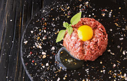 Raw minced meat, vegetables with salt and spices, selective focus. Raw minced meat, vegetables with salt and spices, on a black background, selective focus Royalty Free Stock Images