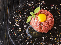 Raw minced meat, vegetables with salt and spices, selective focus. Raw minced meat, vegetables with salt and spices, on a black background, selective focus Stock Photography
