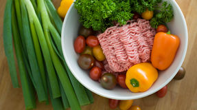 Raw Minced Meat and Vegetables. Raw Minced Meat in a White Bowl and Vegetables on Wooden Cutting Board Royalty Free Stock Image