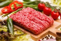 Raw minced meat with vegetables on wooden board Royalty Free Stock Photo