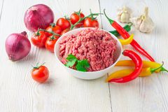 Raw minced pork in a plate and fresh vegetables on a table close. Raw minced pork in a white plate and fresh tomato, pepper, onion, garlic on a rustic table Stock Photography