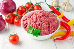 Raw minced pork in a plate and fresh vegetables on a table close. Raw minced pork in a white plate and fresh tomato, pepper, onion, garlic on a rustic table Stock Photo