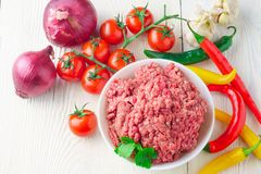 Raw minced pork in a plate and fresh vegetables on a table close. Raw minced pork in a white plate and fresh tomato, pepper, onion, garlic on a rustic table Stock Images