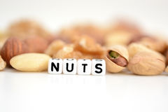 "Raw mixed nuts and the word ""nuts"" spelled by tiled letter beads spread on a white table. Raw mixed nuts and the word ""nuts"" spelled by plastic royalty free stock photo"