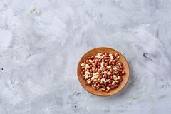 Raw mixed peanuts in wooden plate isolated over white textured background, top view, close-up. Mix of raw shelled peanuts in wooden plate isolated over white stock image