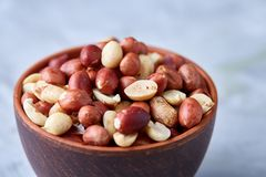 Raw mixed peanuts in wooden plate isolated over white textured background, top view, close-up. Mix of raw shelled peanuts in wooden plate isolated over white royalty free stock image