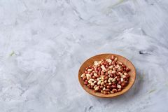 Raw mixed peanuts in wooden plate over white textured background, top view, close-up. Mix of raw shelled peanuts in wooden plate over white textured background royalty free stock photos