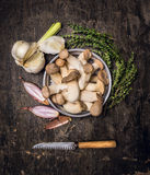 Raw Mushrooms in bowl with thyme , fresh garlic , onions and vintage knife. On dark wooden background, Preparation, top view Stock Photo