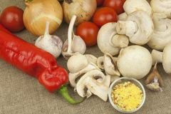 Raw mushrooms on a cutting board. Preparation of Champignons in the kitchen. Spices for food preparation. Royalty Free Stock Images