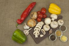 Raw mushrooms on a cutting board. Preparation of Champignons in the kitchen. Spices for food preparation. Stock Image