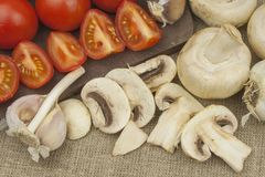 Raw mushrooms on a cutting board. Preparation of Champignons in the kitchen. Spices for food preparation. Royalty Free Stock Photos