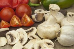 Raw mushrooms on a cutting board. Preparation of Champignons in the kitchen. Spices for food preparation. Royalty Free Stock Photography