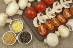 Raw mushrooms on a cutting board. Preparation of Champignons in the kitchen. Spices for food preparation. Stock Photography
