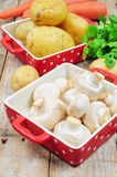 Raw mushrooms and potatoes. In red trays Royalty Free Stock Images