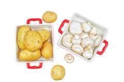 Raw mushrooms and potatoes in red trays, isolated Stock Image