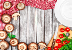 Raw mushrooms, tomatoes and parsley. On a wooden background Stock Photography