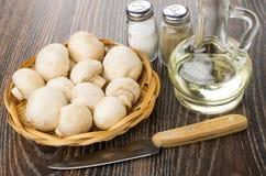 Raw mushrooms in wicker basket, salt, pepper, vegetable oil, kni Stock Images