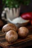 Raw mushrooms on wooden board. Three mushrooms on kitchen. Raw mushrooms on wooden board. Three mushrooms on kitchen Stock Photo
