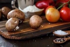 Raw mushrooms on wooden board. Three mushrooms on kitchen. Raw mushrooms on wooden board. Three mushrooms on kitchen Stock Photos