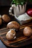 Raw mushrooms on wooden board. Three mushrooms on kitchen. Raw mushrooms on wooden board. Three mushrooms on kitchen Stock Image