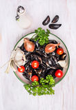 Raw mussels in bowl with water ,spices and oil. On white wooden background,preparation, top view Stock Image