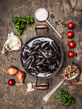Raw mussels in pan with water , herbs and spices , preparation. Raw mussels in pan with water , herbs and spices on dark wooden background, top view Royalty Free Stock Images